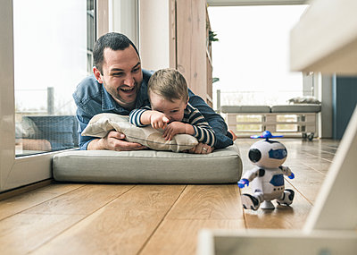 Excited father and son lying on a mattress at home watching a toy robot - p300m2104377 by Uwe Umstätter