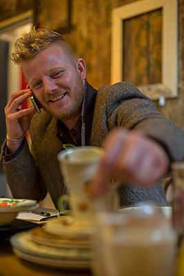 Man talking on cell phone at table - p429m767861 by dotdotred