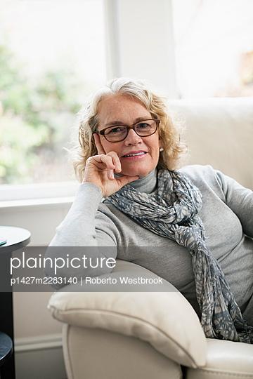 Portrait of happy senior woman sitting on sofa - p1427m2283140 by Roberto Westbrook