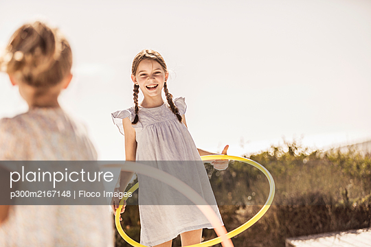 Two happy girls playing with hoola hoop on terrace of a beach house - p300m2167148 by Floco Images