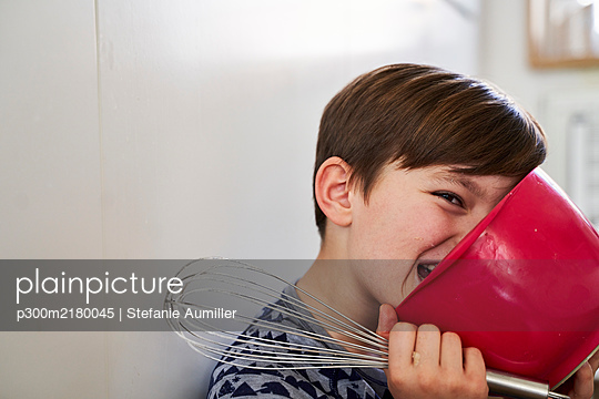Portrait of boy with red mixing bowl and egg beater in kitchen - p300m2180045 by Stefanie Aumiller