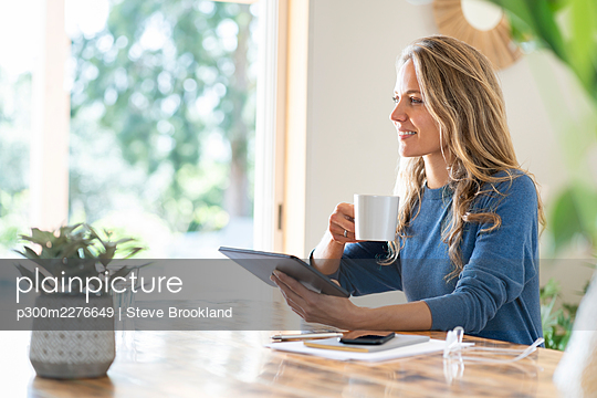 Smiling businesswoman drinking coffee while holding tablet sitting at table looking away - p300m2276649 by Steve Brookland