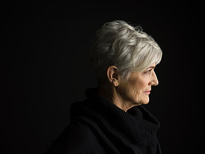 Profile portrait senior woman with short gray hair looking away against black background - p1192m1403605 by Hero Images