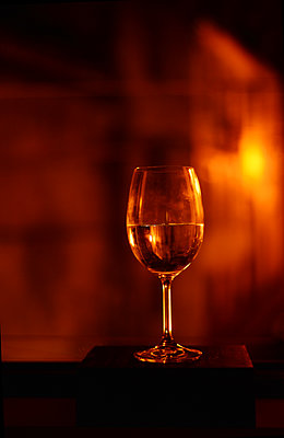 Wine glass against red light - p1695m2290965 by Dusica Paripovic