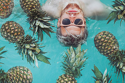 Young man in swiming pool surrounded by pineapples - p300m1355916 by Retales Botijero