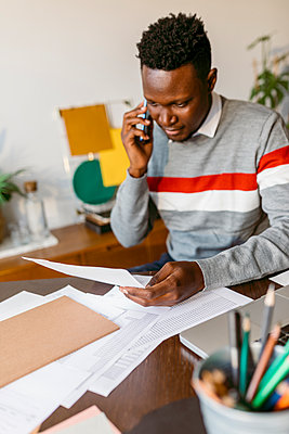 Male entrepreneur talking on smart phone while holding document in home office - p300m2241181 by Valentina Barreto