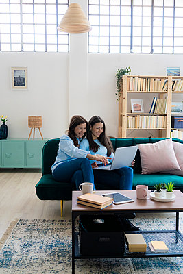 Smiling businesswoman assisting daughter using laptop on sofa at home - p300m2265442 by Giorgio Fochesato
