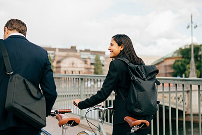 Smiling businesswoman looking at businessman while walking with bicycles on bridge in city - p426m2145705 by Maskot