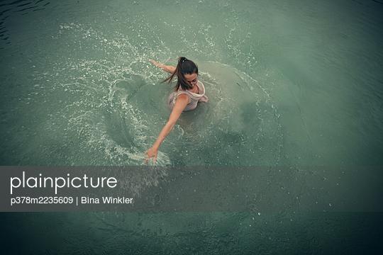 Woman swirling in lake - p378m2235609 by Bina Winkler
