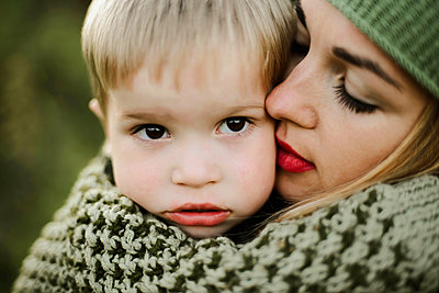 Close -up young mother hugs her little pretty son outdoor - p1166m2095453 by Cavan Images