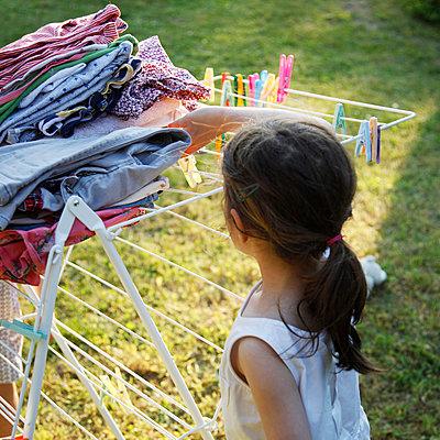Mädchen steht vor Wäscheständer - p1270m1106197 von Camille Malissen