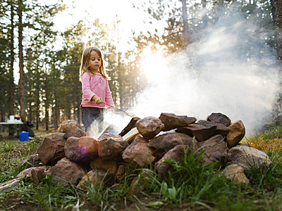 Girl (4-5) roasting marshmallow above campfire, Wasatch Cache National Forest - p1427m2213553 by Jessica Peterson