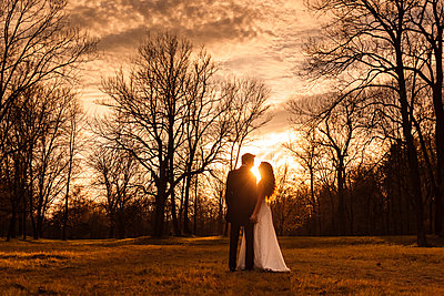 Happy bridal couple embracing in park - p300m2059934 by Christina Falkenberg