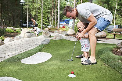 Man and baby boy playing mini golf - p312m1495387 by Helena Christerdotter