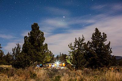 Campsite in remote field under cloudy sky - p555m1412136 by Adam Hester
