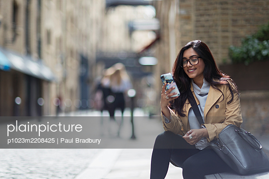 Smiling businesswoman using smart phone on city sidewalk - p1023m2208425 by Paul Bradbury