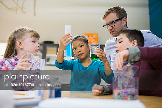 Teacher and elementary students conducting scientific experiment - p1192m1016776f by Hero Images