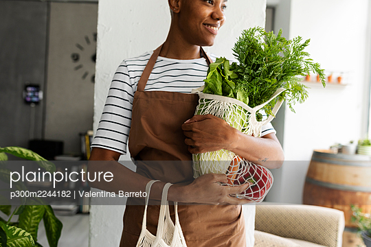 Pretty woman in apron carrying net with fresh vegetables - p300m2244182 by Valentina Barreto