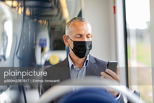 Businessman using smart phone in tram during COVID-19 - p300m2287617 by Emma Innocenti