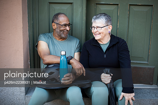 Smiling couple sitting against doorway of house - p426m2238931 by Maskot