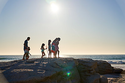 Family walking on rocks on sunny ocean beach, Cape Town, South Africa - p1023m2200863 by Trevor Adeline
