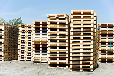 Stack of pallets arranged in an order against the sky - p1025m780398f by Björn Andrén