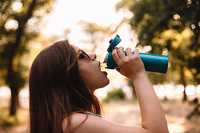 Young woman drinking water from reusable bottle in summer park - p1166m2212442 by Cavan Images