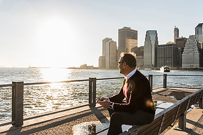 USA, Brooklyn, relaxed man with smartphone sitting on bench looking at view - p300m1206229 by Uwe Umstätter