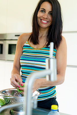 Portrait of smiling dark-haired woman preparing saladin kitchen at home - p300m2060160 by harrylidy