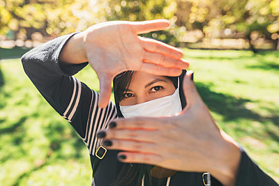 Close-up of young woman wearing mask looking through finger frames in park - p300m2206594 by Daniel Sierralta