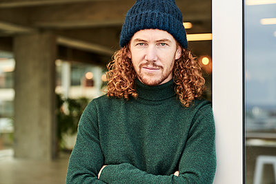 Handsome male hipster wearing knit hat while leaning on window at studio apartment - p300m2225553 by Jo Kirchherr