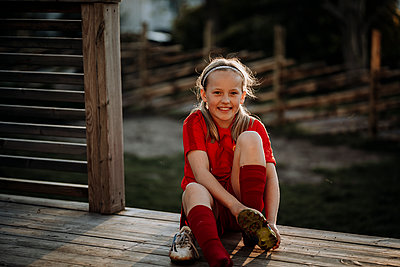 Smiling girl putting football shoes on - p312m2208147 by Anna Johnsson