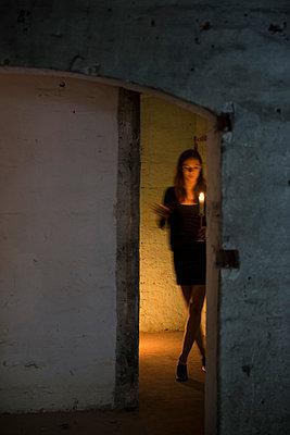 Frau mit Kerze in einem Keller - p335m1041640 von Andreas Körner