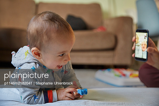 Father shows baby boy pictures on smartphone, Stay at home due to Covid-19 - p1146m2182041 by Stephanie Uhlenbrock