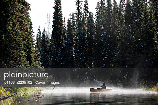 Man paddling boat on a remote lake on a foggy misty day surrounded by trees - p1166m2235102 by Cavan Images