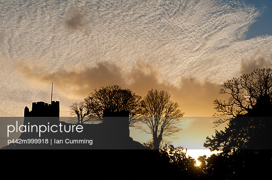 Silhouette of Lewes Castle with mackerel sky behind at dusk; Lewes, East Sussex, England - p442m999918 by Ian Cumming