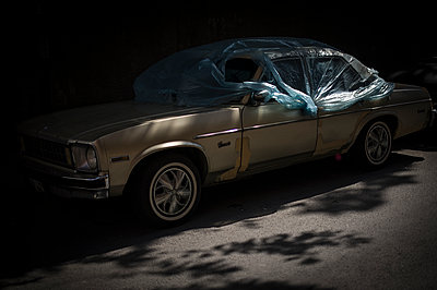 Old car in the street with plastic and shadows - p1007m1134837 by Tilby Vattard