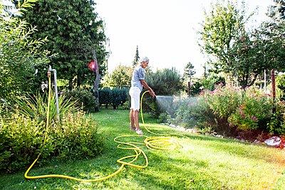 Rentnerin gießt ihren Garten - p1093m2192932 von Sven Hagolani
