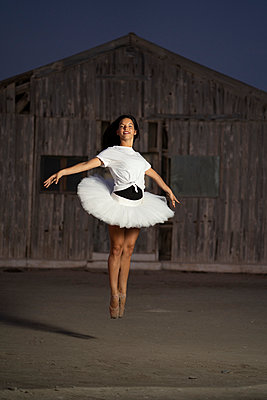 Ballerina dancing in front of a wooden hut in the evening - p300m2155629 by Manu Padilla Photo