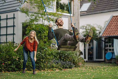 Woman pushing man, sitting on swing in garden - p300m2166715 by Kniel Synnatzschke