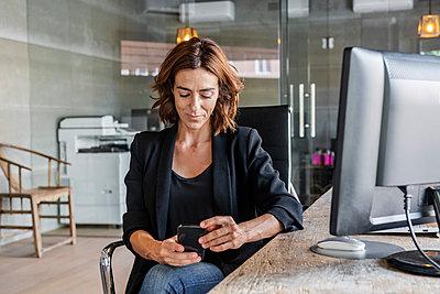 Beautiful woman using mobile phone while sitting at office - p300m2220605 by Javier De La Torre Sebastian
