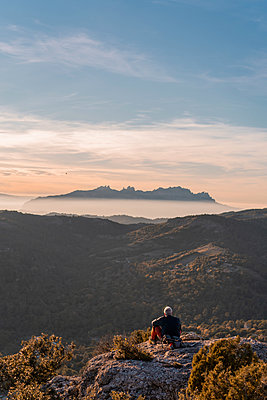 Senior man looking at mountain while sitting at cliff during hiking - p300m2298733 by VITTA GALLERY
