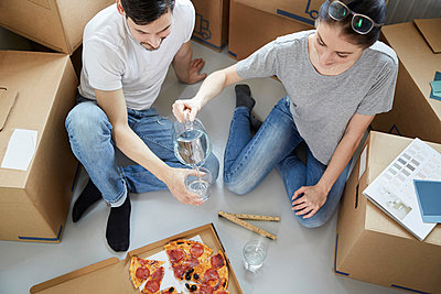 Woman serving water to man while having pizza during relocation of new house - p426m2097626 by Maskot