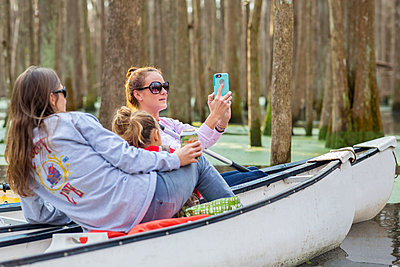 Caucasian family taking cell phone photographs in canoes on river - p555m1413399 by Marc Romanelli