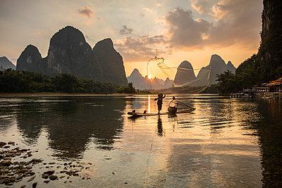 Cormorant fisherman throwing net on Li River at dawn, Xingping, Yangshuo, Guangxi, China - p651m2271089 by Jeremy Flint photography