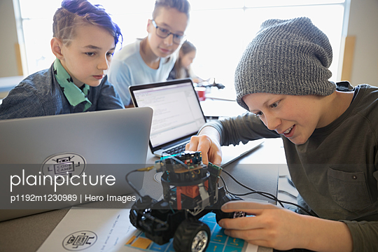 Pre-adolescent boys and girl assembling and programming robotics at laptops in classroom - p1192m1230989 by Hero Images