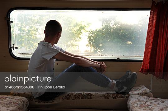 Jugendlicher blickt durch das Fenster seines Wohnwagen - p1468m1584990 von Philippe Leroux