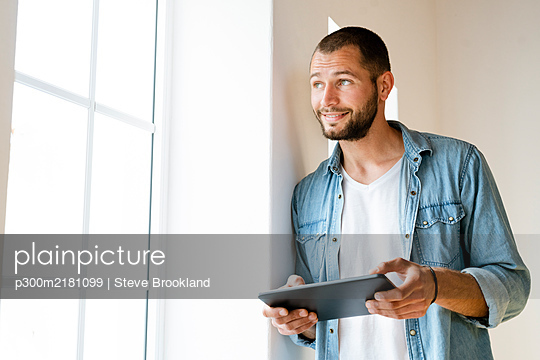 Young smiling man at home holding his tablet and looking outside of his window - p300m2181099 by Steve Brookland