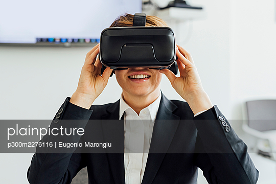 Smiling businesswoman with wearable computer in office - p300m2276116 by Eugenio Marongiu