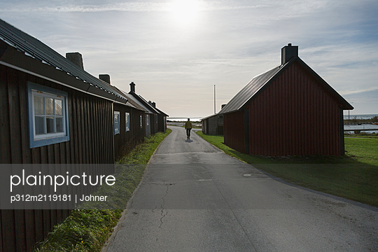 Person on village road - p312m2119181 by Johner